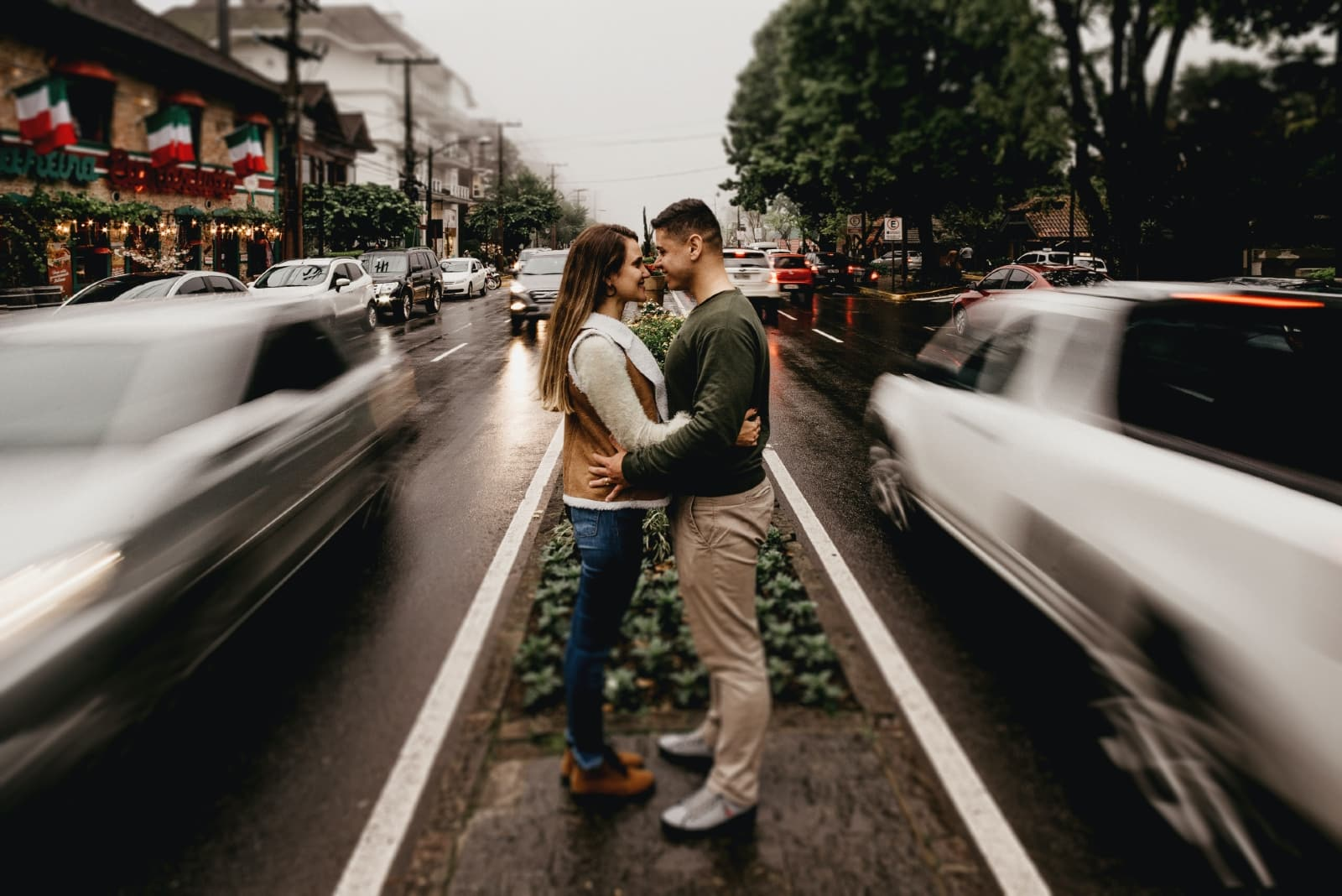 man and woman making eye contact while standing near road