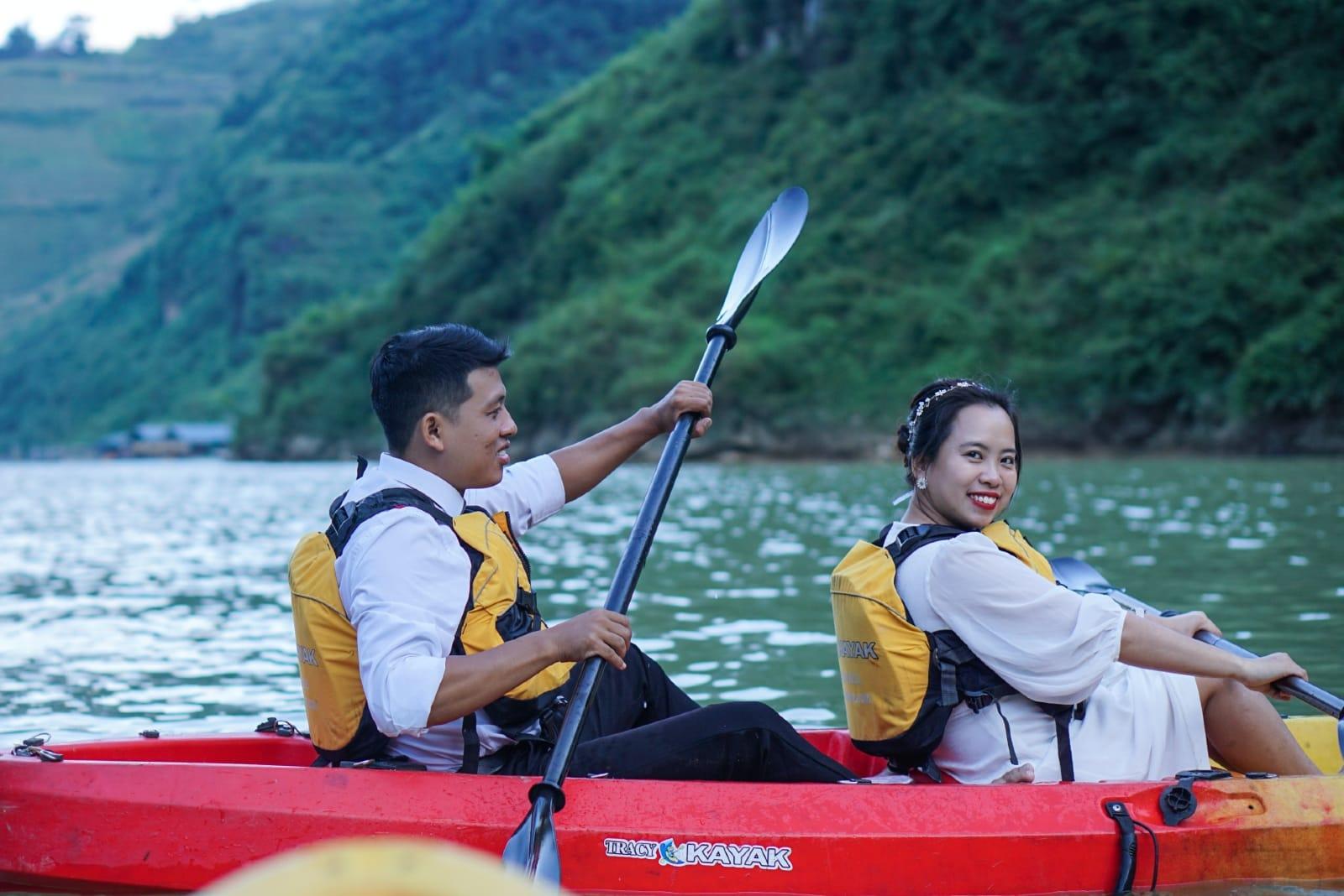 man and woman riding red kayak on lake