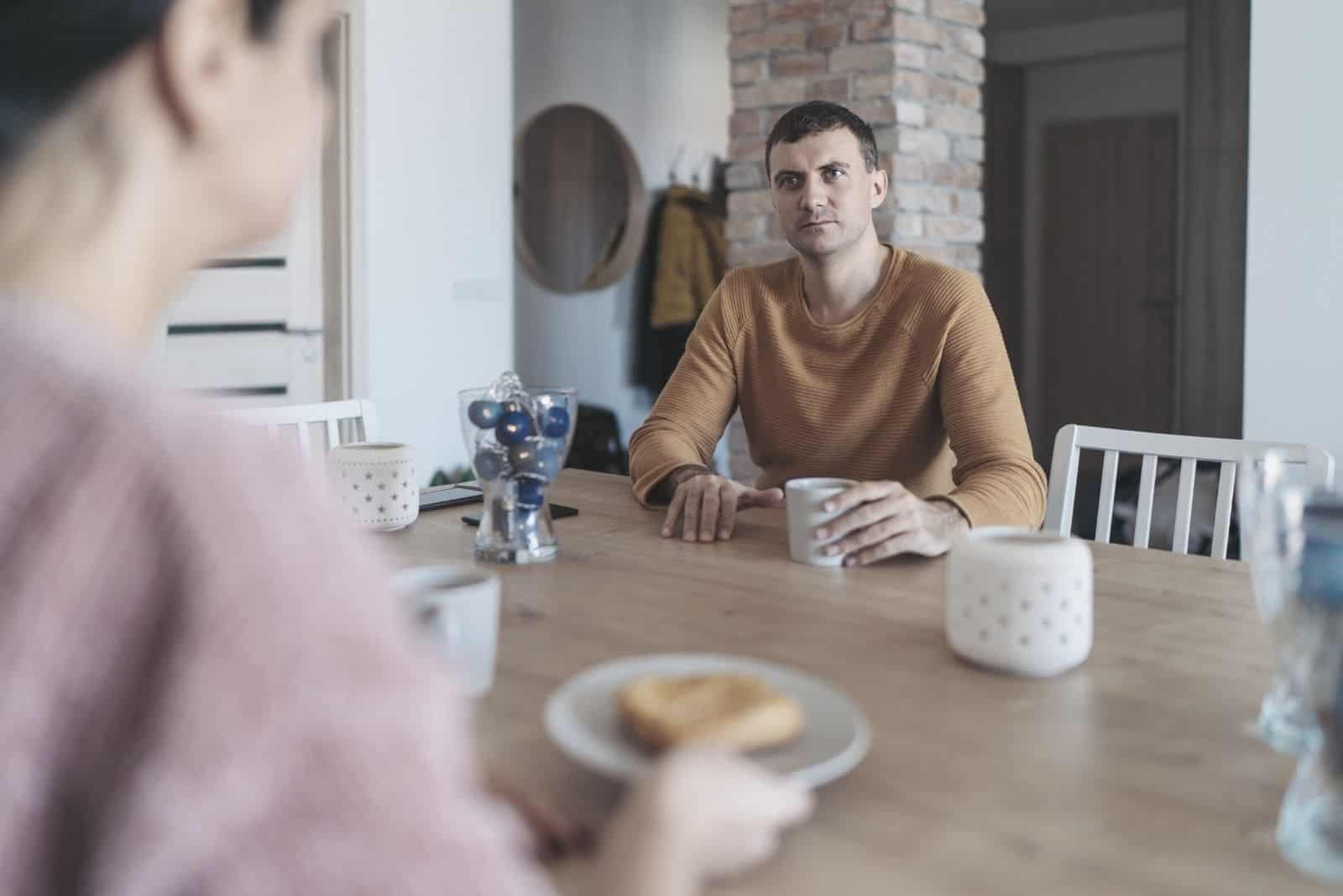 couple sitting in the kitchen having serious conversation during breakfast