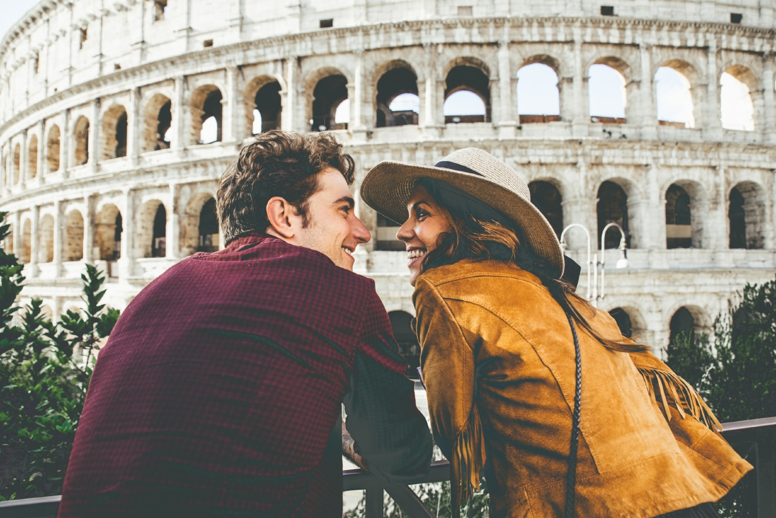 man and woman making eye contact while sitting near colosseum