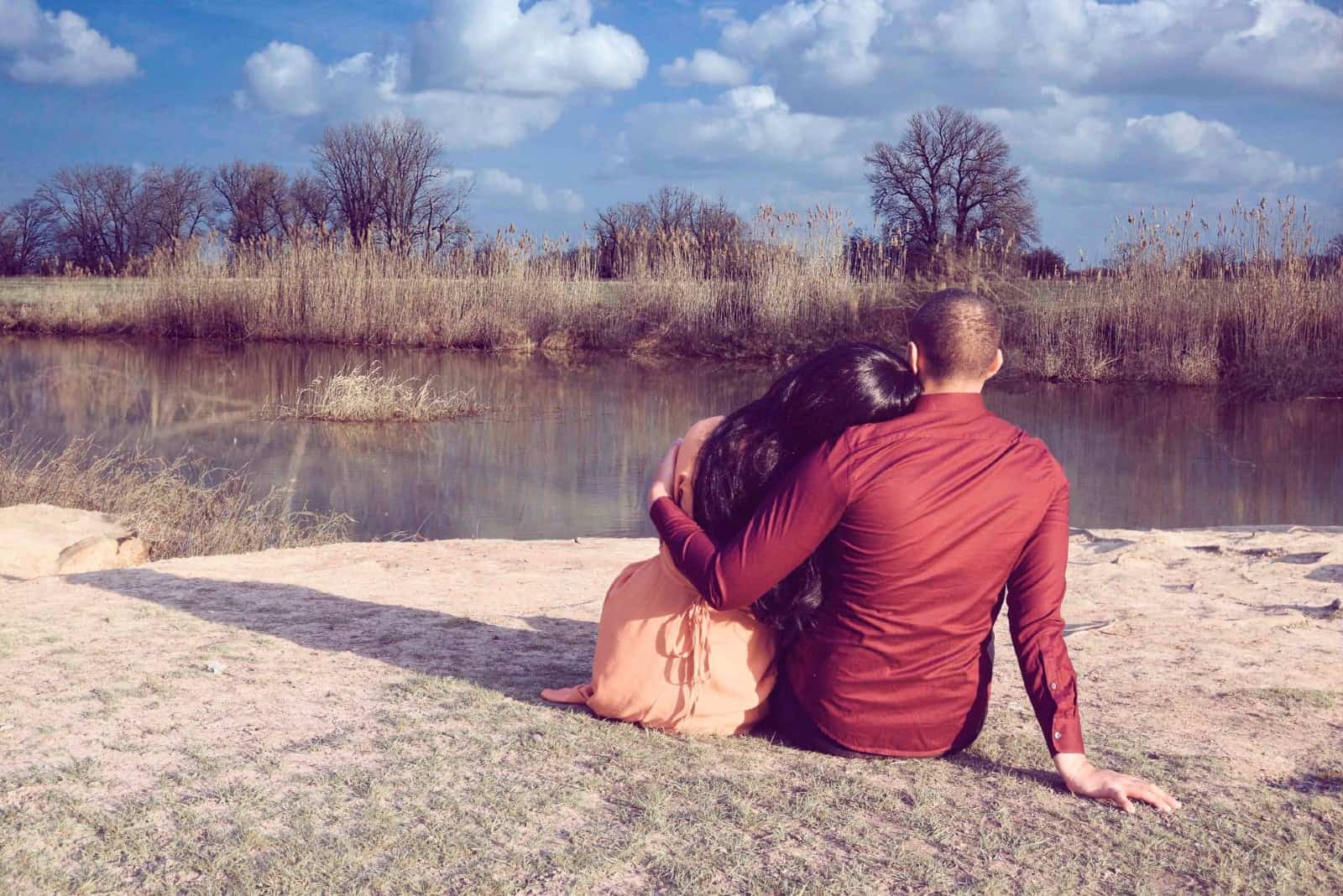 man and woman hugging while sitting near water