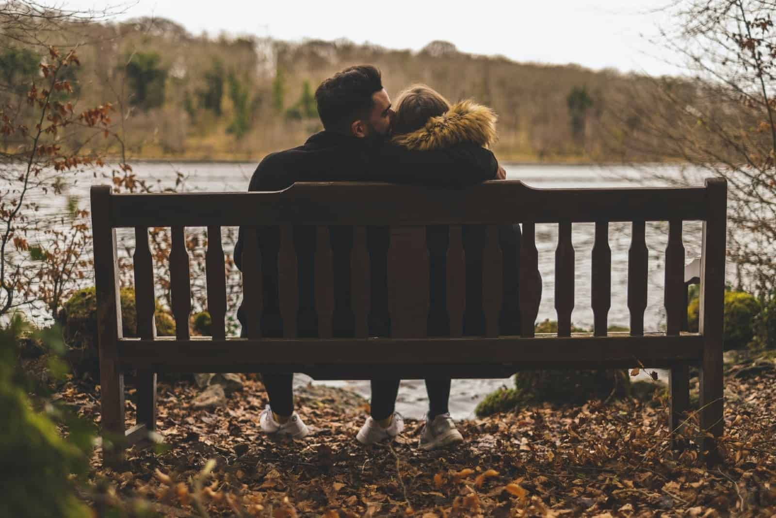 man kissing woman while sitting on bench