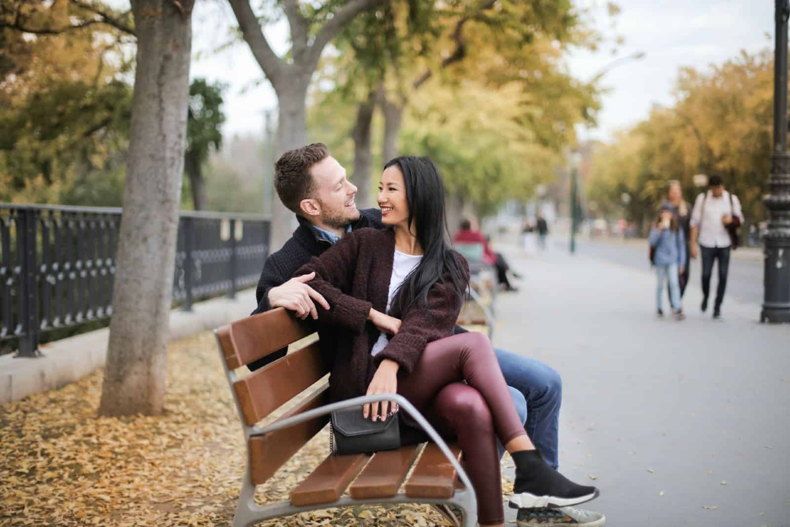 man and woman making eye contact while sitting on bench