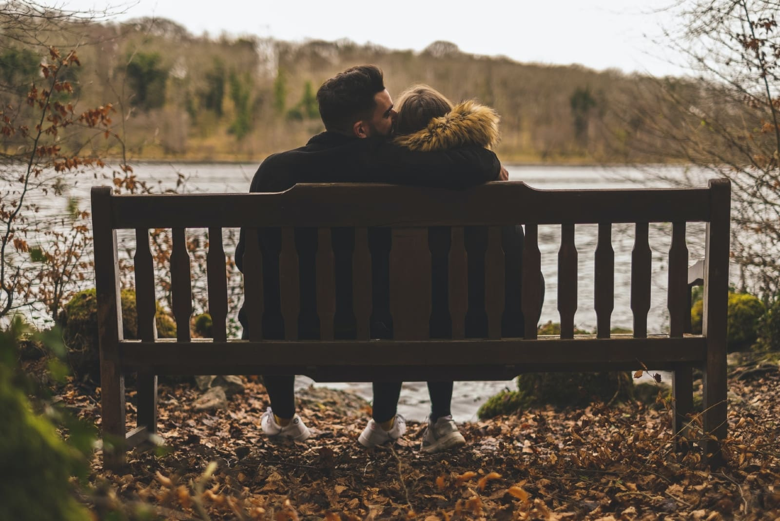 man kissing woman's head while sitting on bench