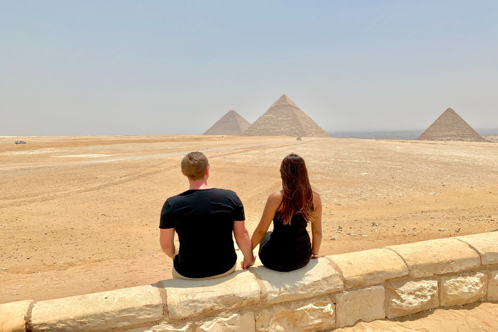 man and woman holding hands while sitting on concrete wall