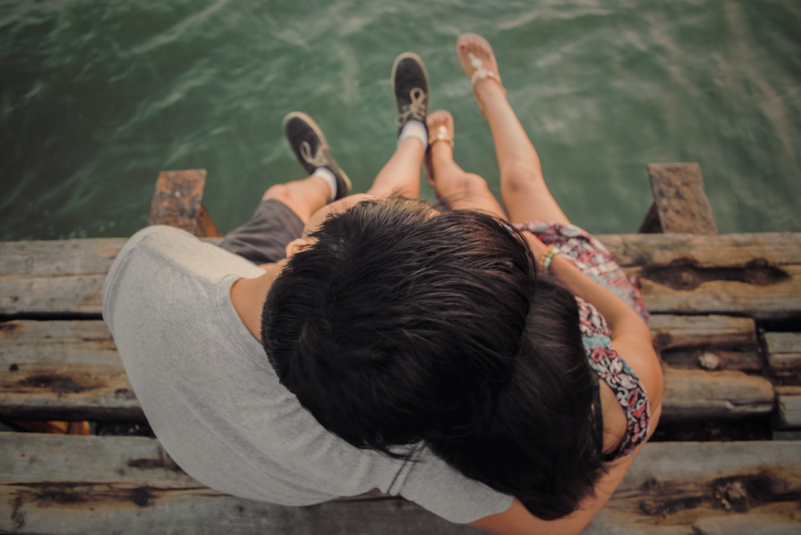 man and woman hugging while sitting on dock