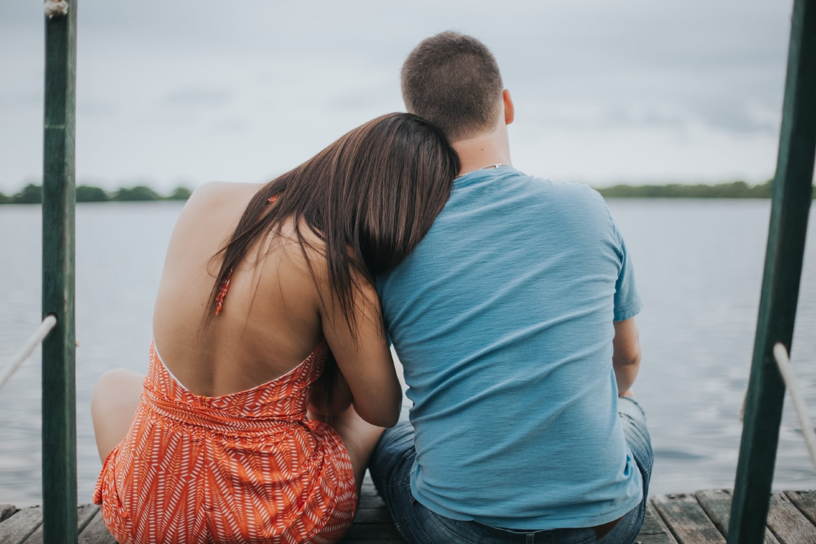 man and woman sitting on dock looking at water