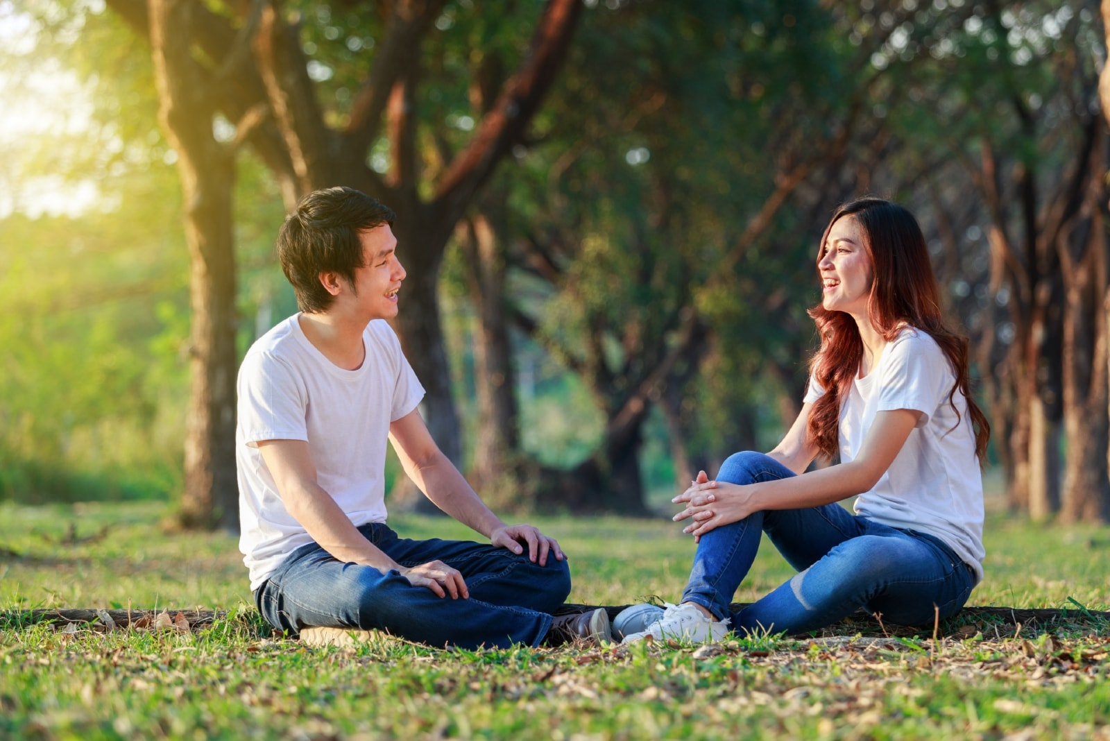 man and woman talking while sitting on grass