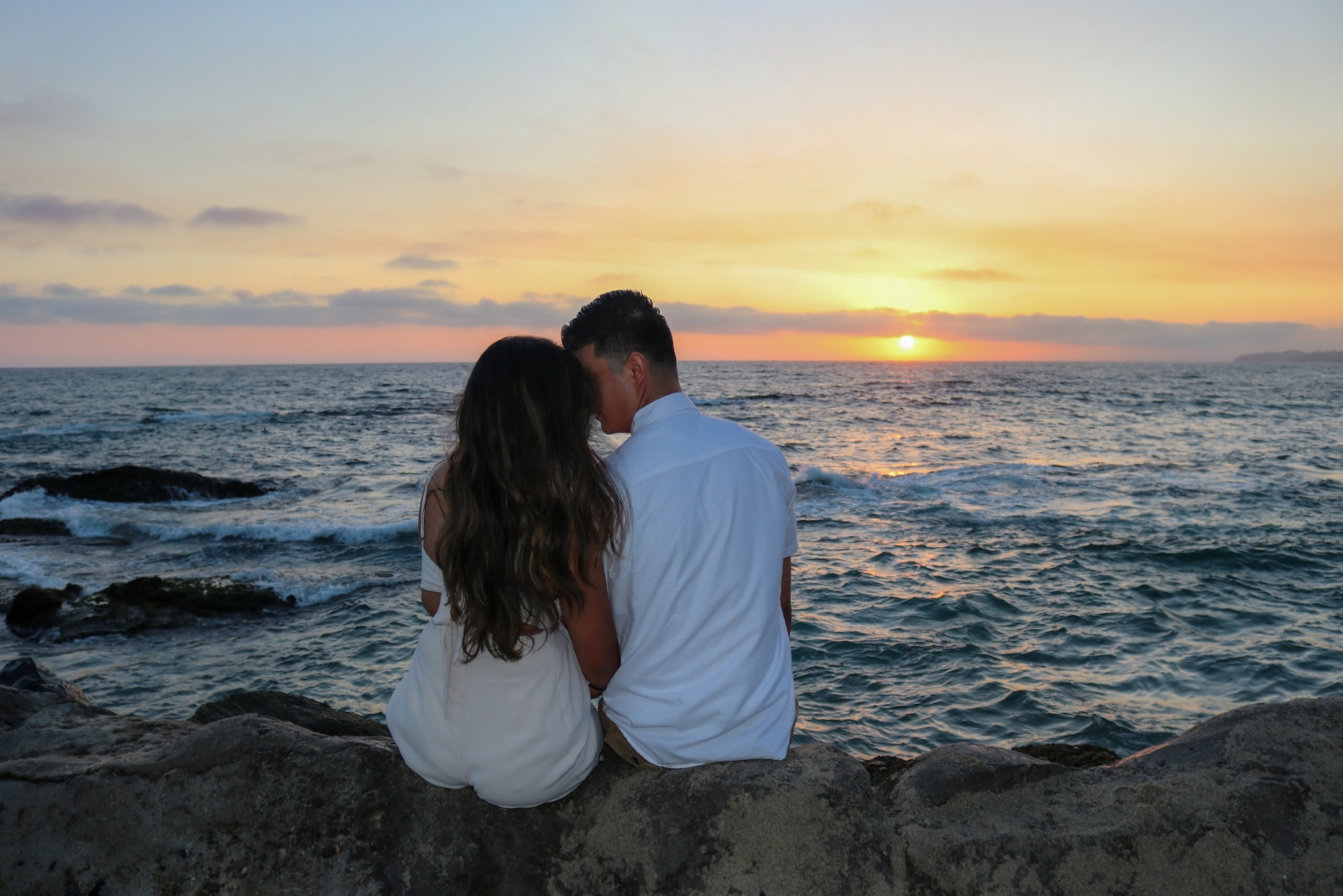 man and woman about to kiss while sitting on rock