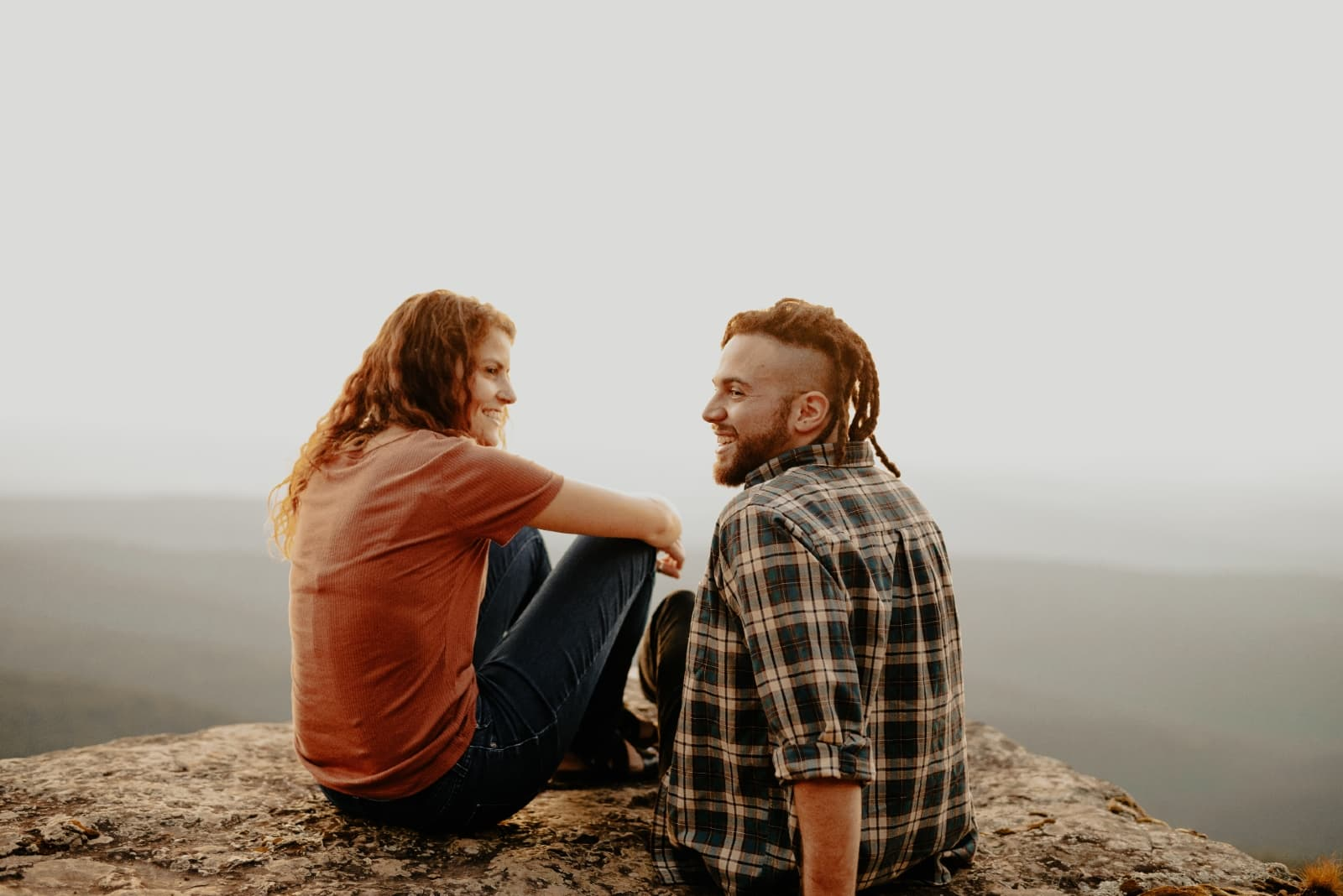 man and woman smiling while sitting on rock