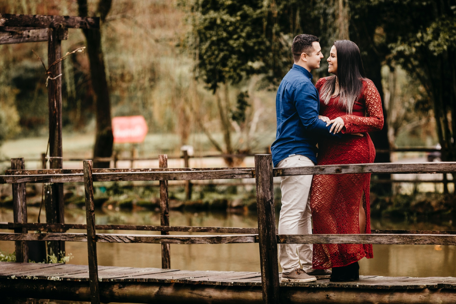 man and woman hugging while standing on bridge