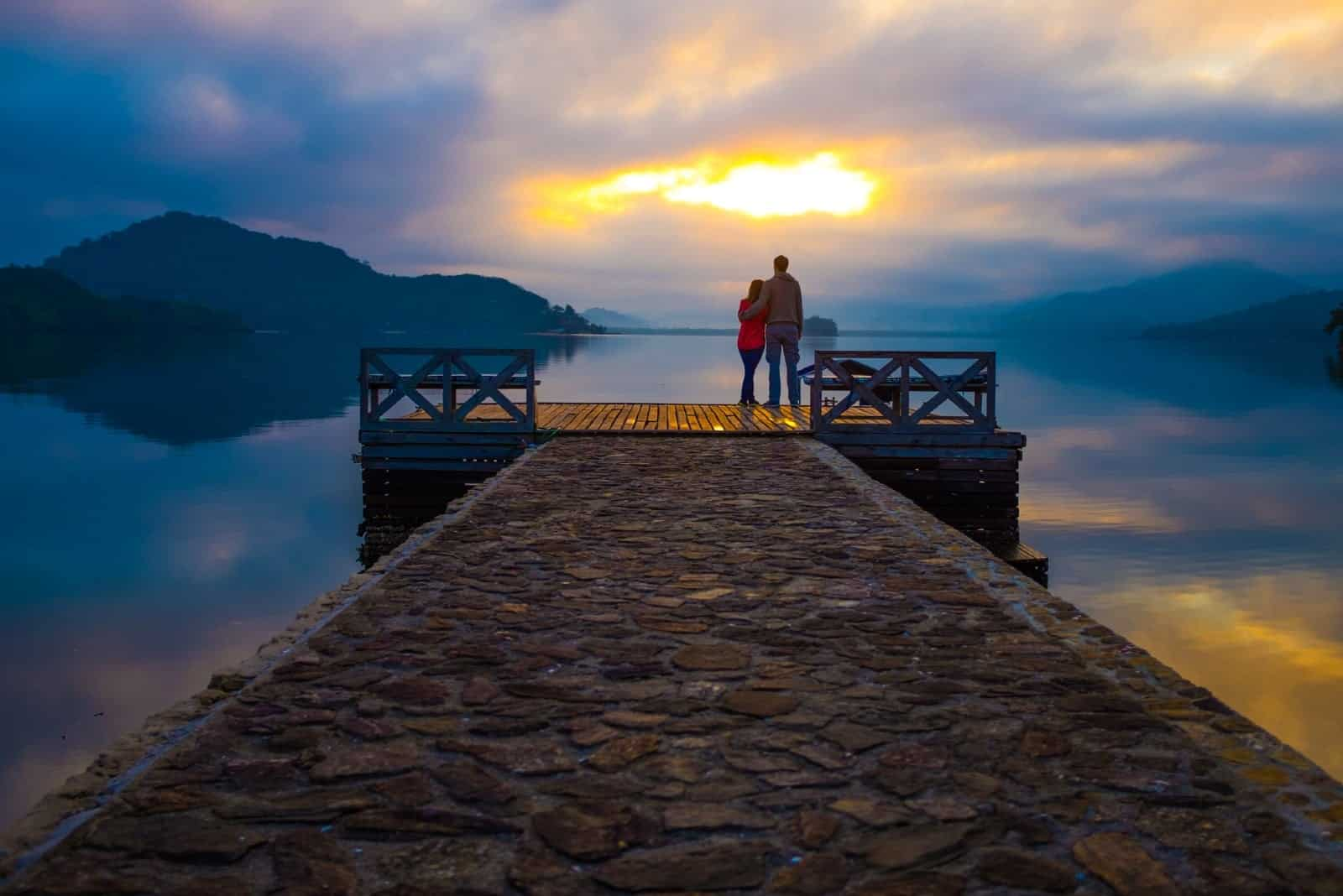 man and woman standing on dock during sunset