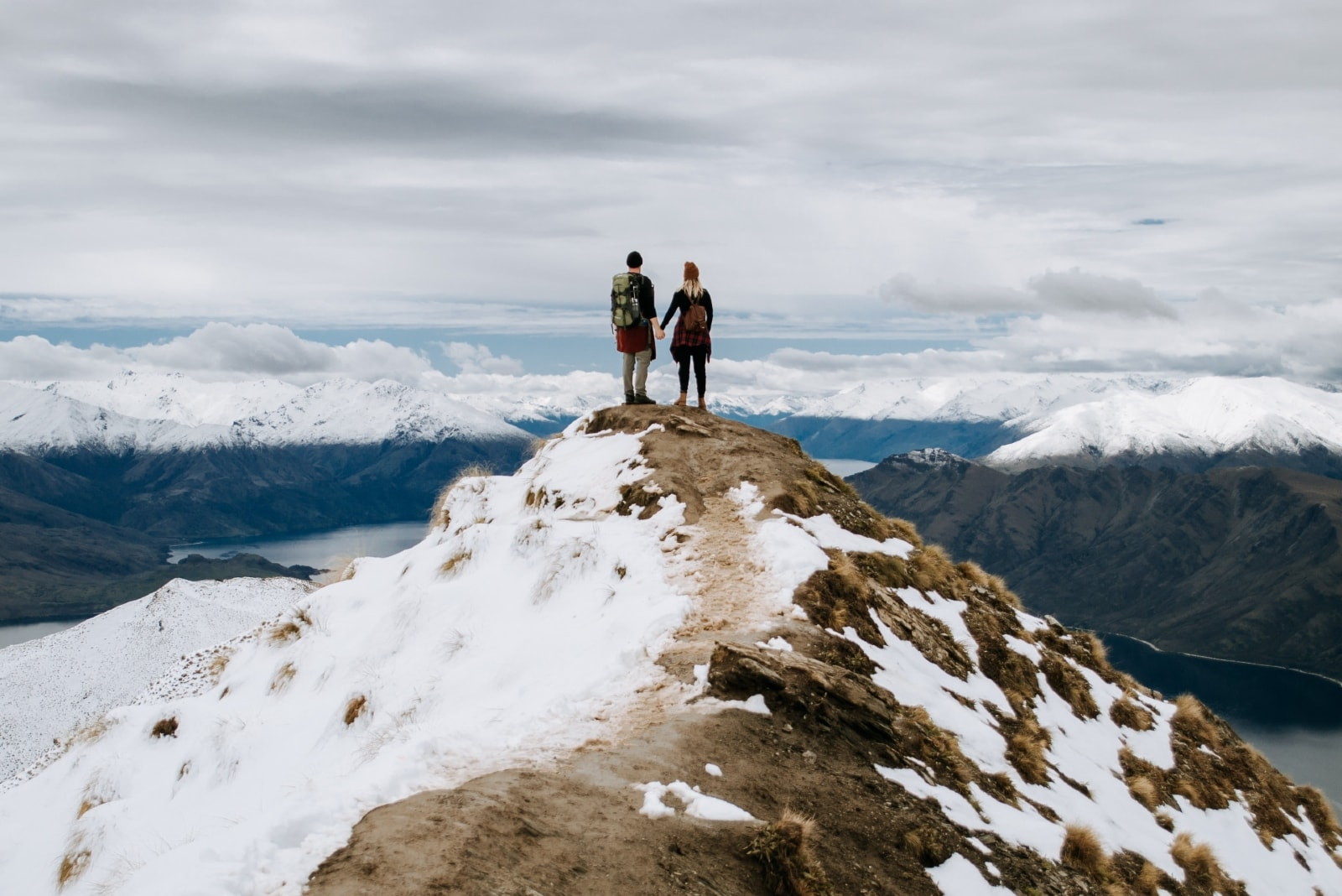 man and woman standing on rock looking at mountain
