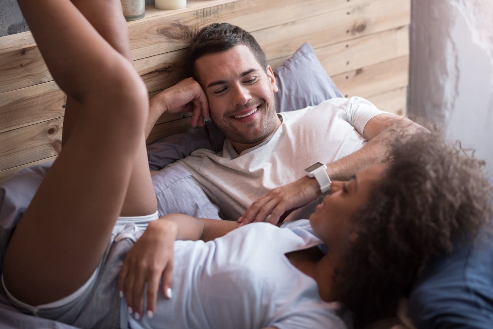 man and woman talking while laying on bed