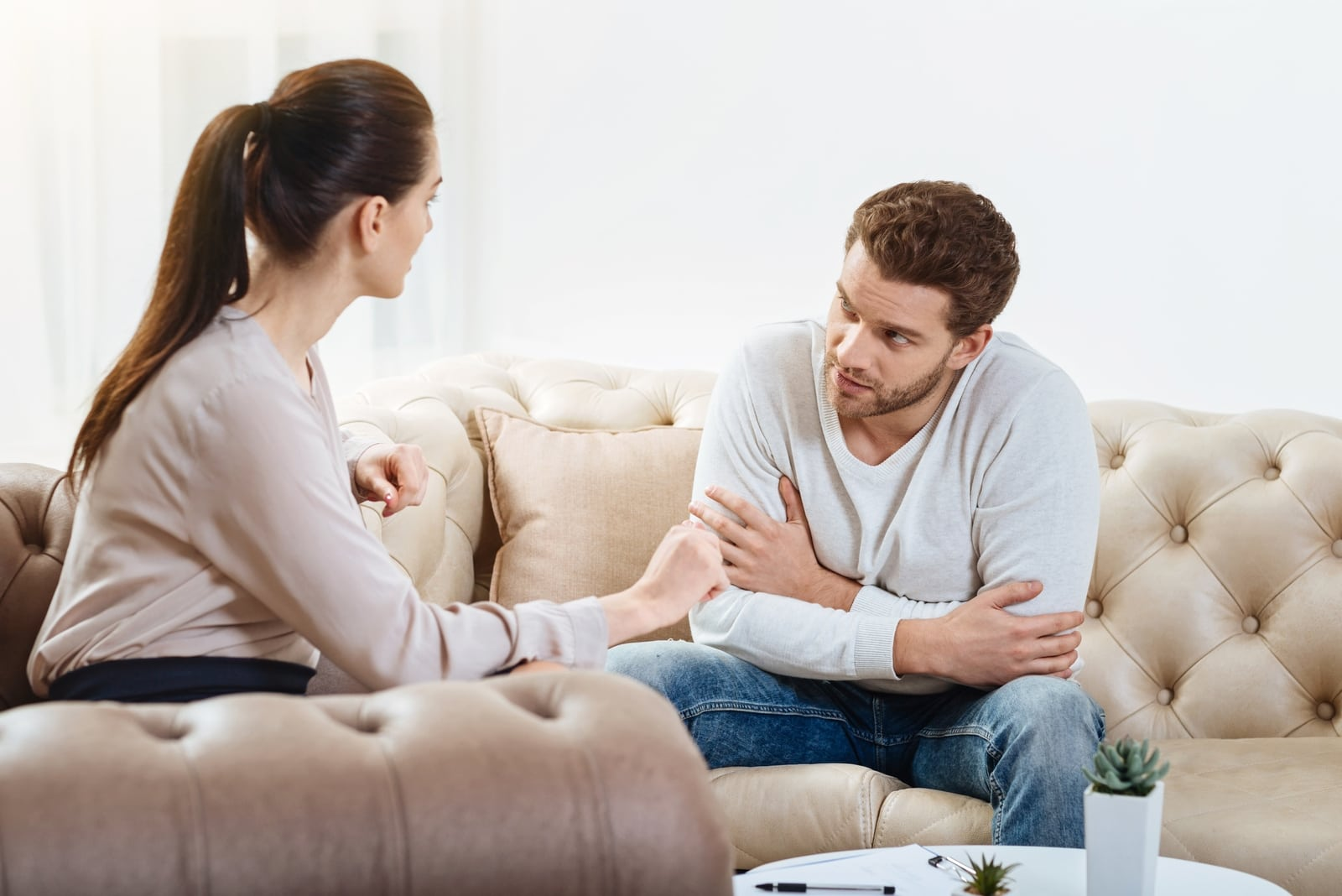 man and woman talking while sitting on sofa