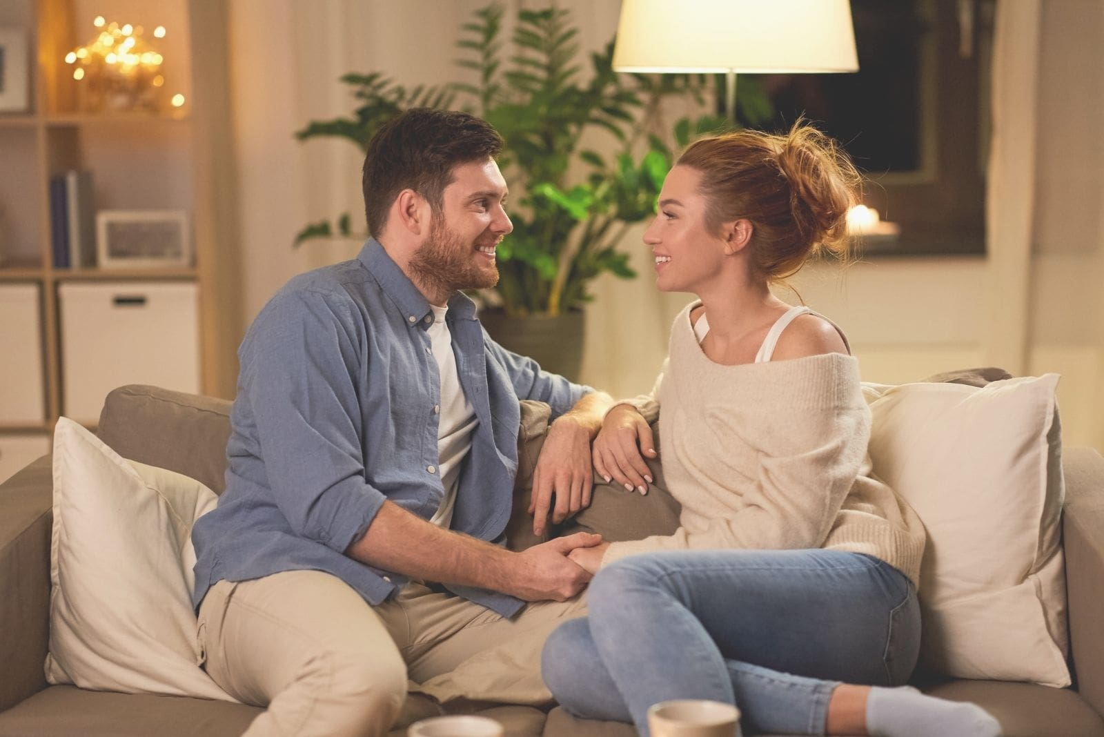 couple talking heart to heart inside the livingroom sitting in one couch