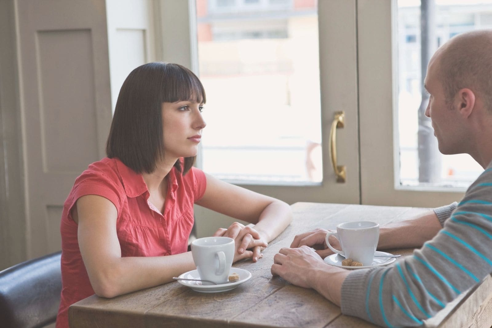 couple talking in cafe seriously sitting near the windows