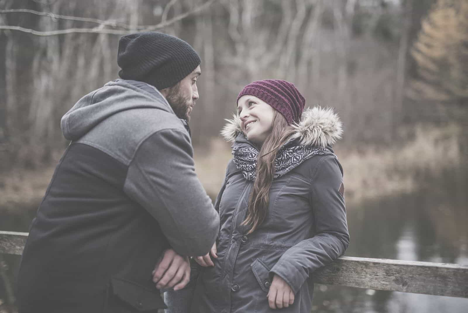 couple talking in the winter outdoors standing and leaning on a wooden railings