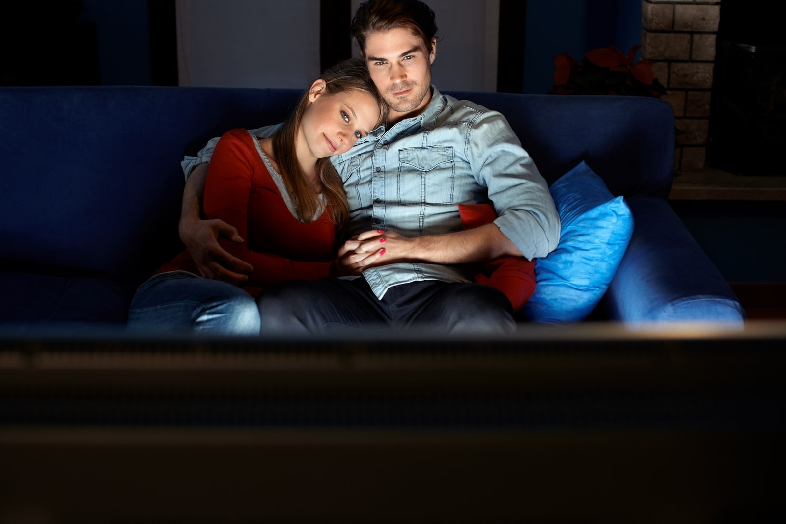 man and woman watching movie while sitting on sofa