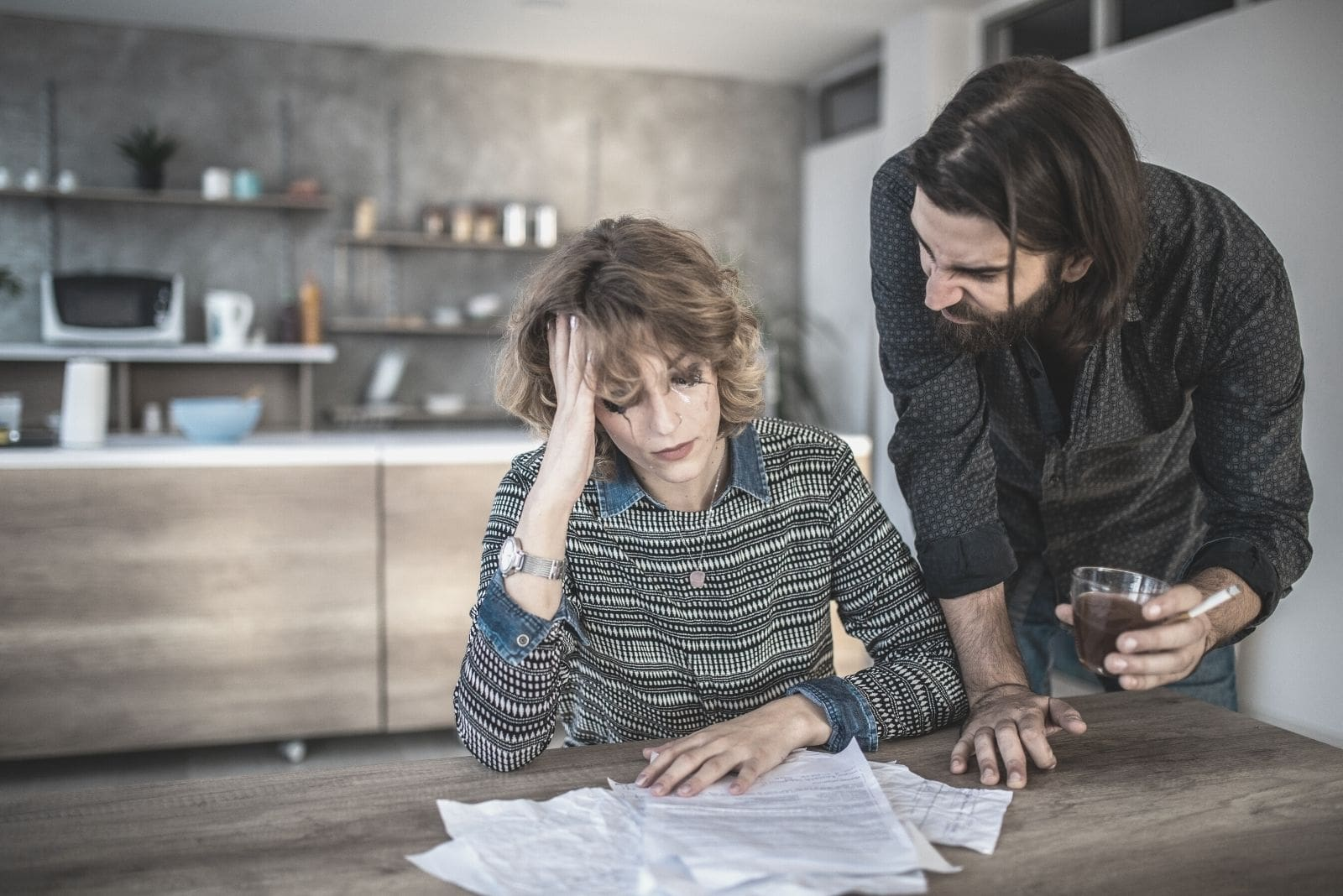 couple with financial problems with the woman crying looking at the bills and the man holding a beer and a cigar inside the kitchen