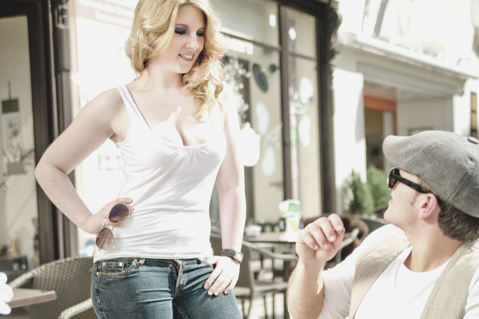 cropped image of sexy woman in white tank top meeting a man in an outdoor cafe