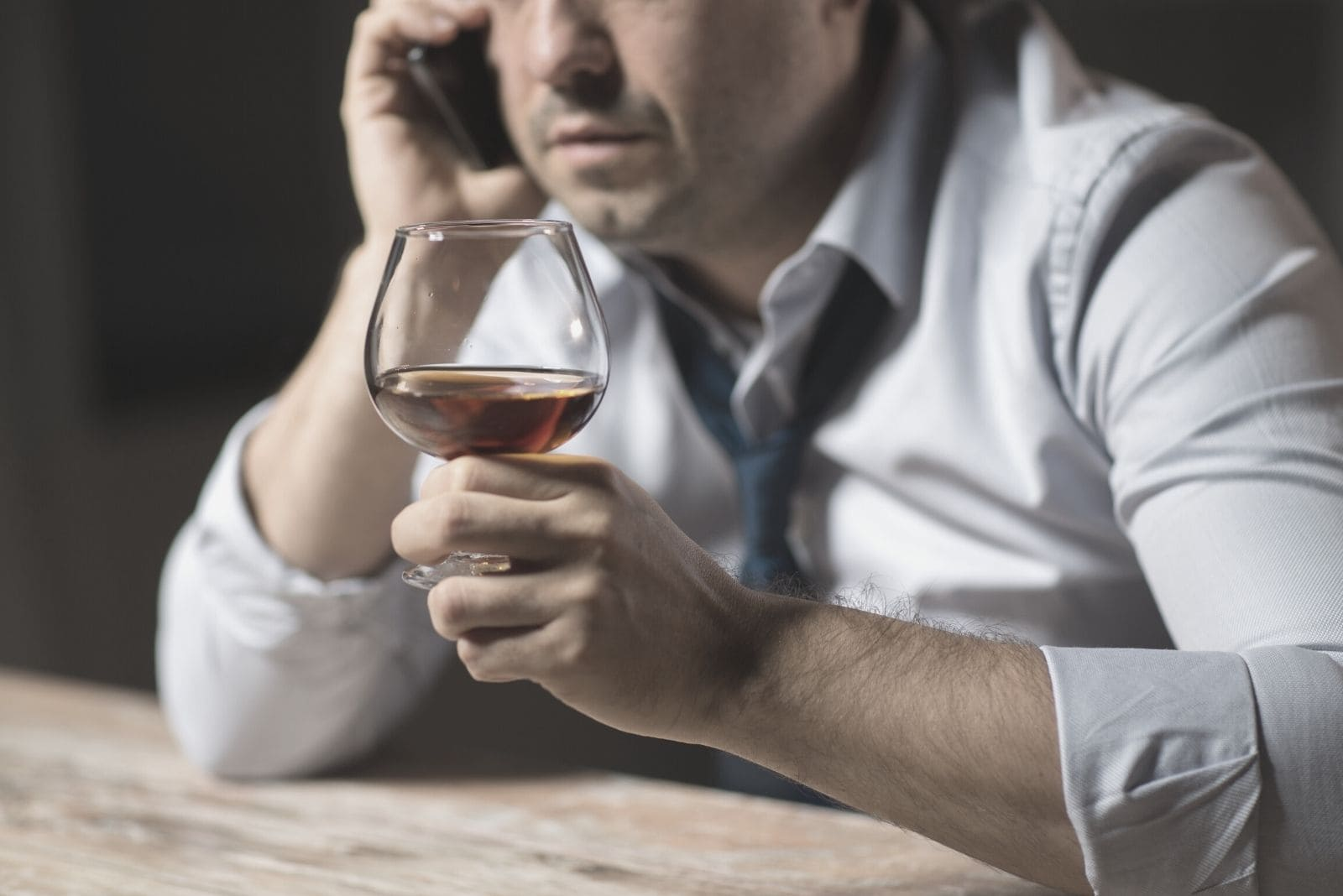 cropped photo of a man drinking alcohol while calling by the phone