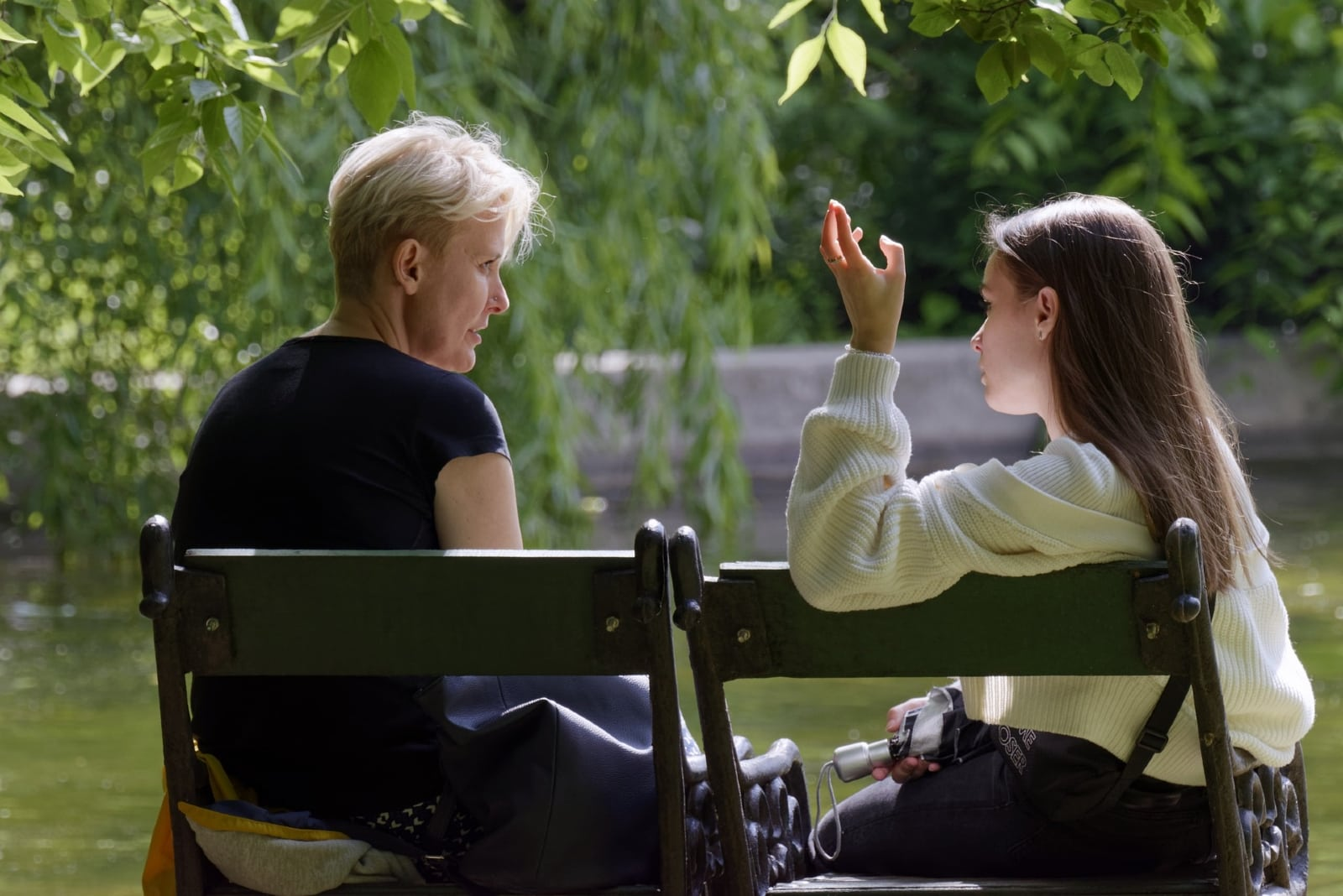 daughter talking to mother while sitting on bench