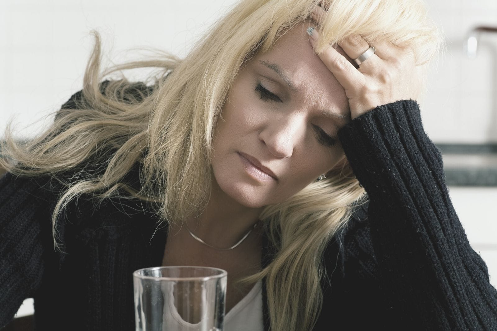 depressed caucasian woman holding her head aching leaning on the table with a glass