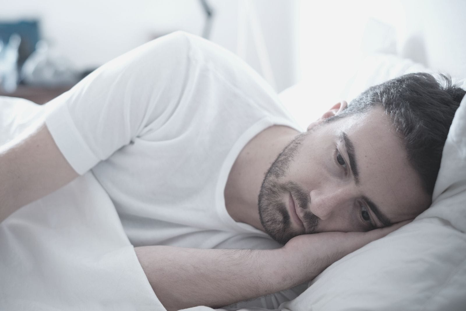 depressed man lying down on bed facing his left side of the bed