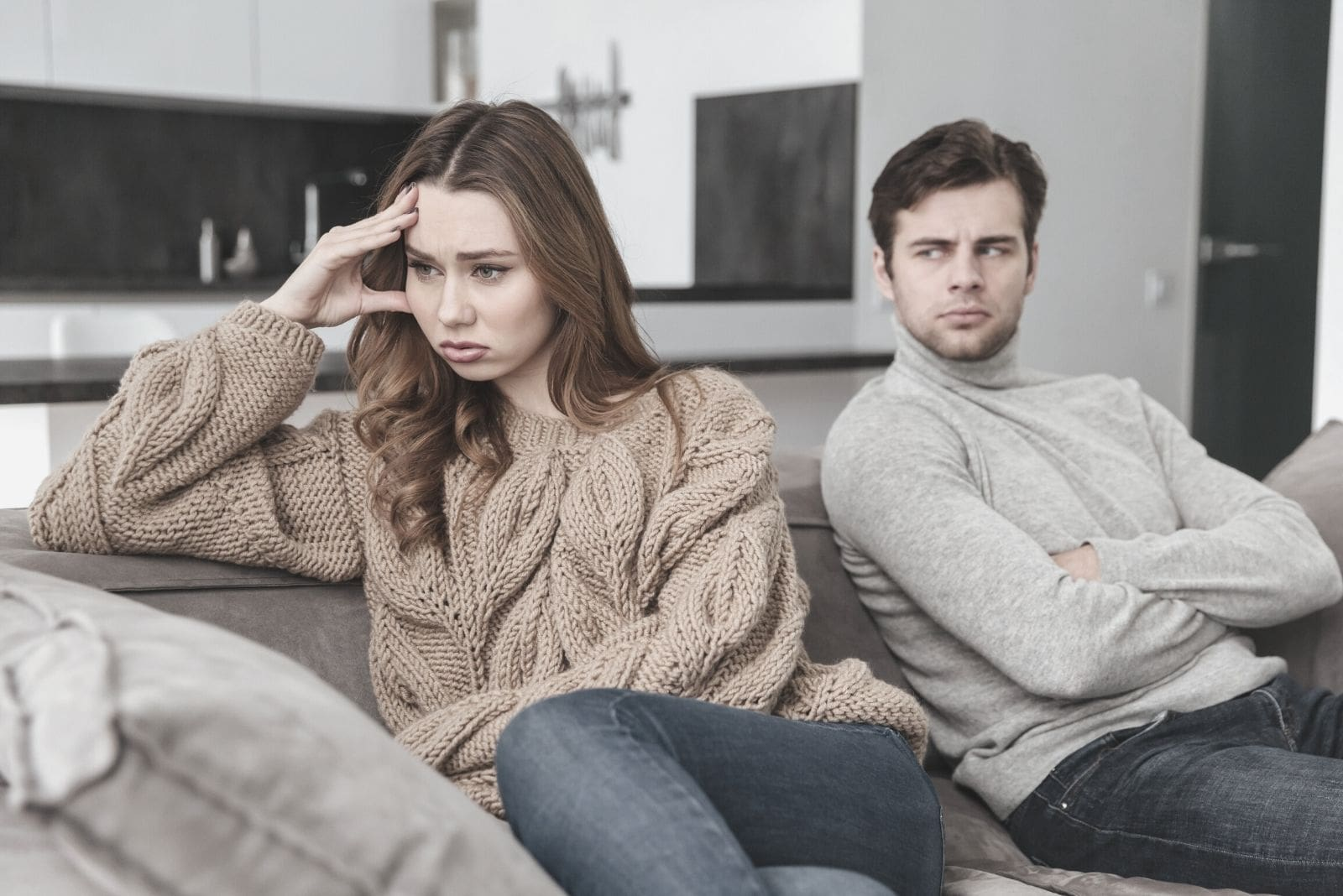 displeased loving couple sitting and not talking to each other