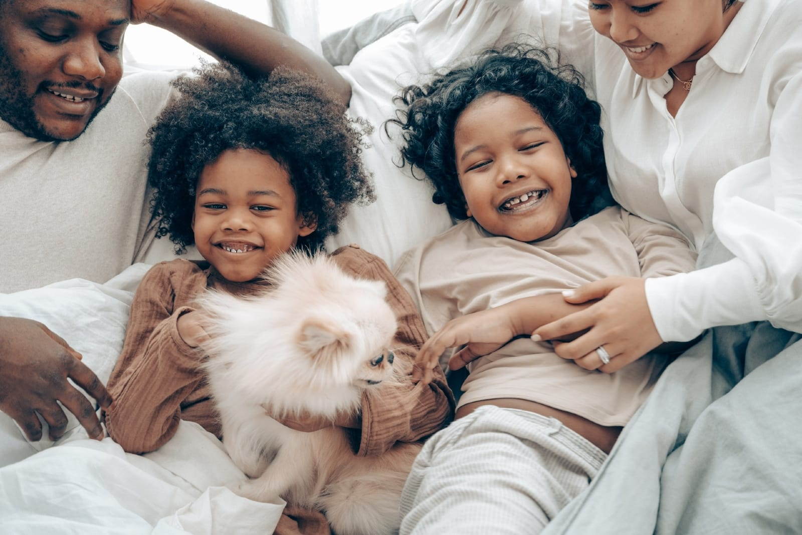 family having fun in bed during weekend