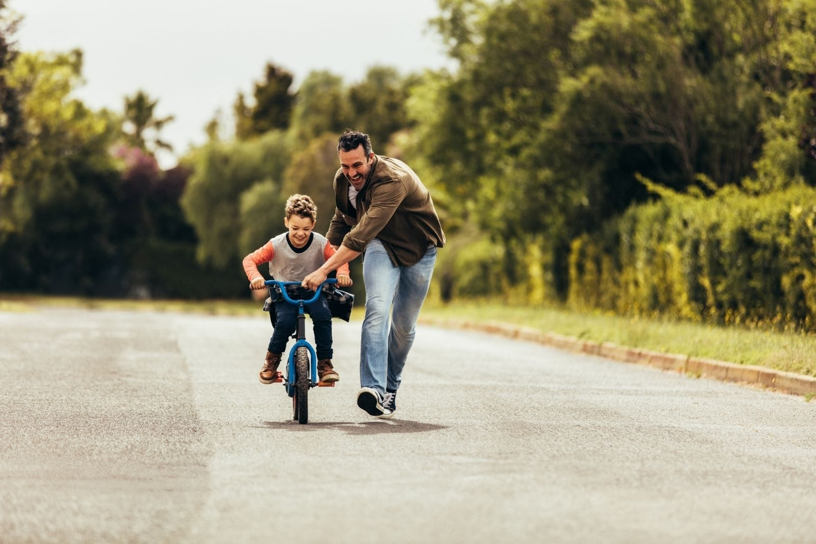 father teaching his son bicycle on an empty street