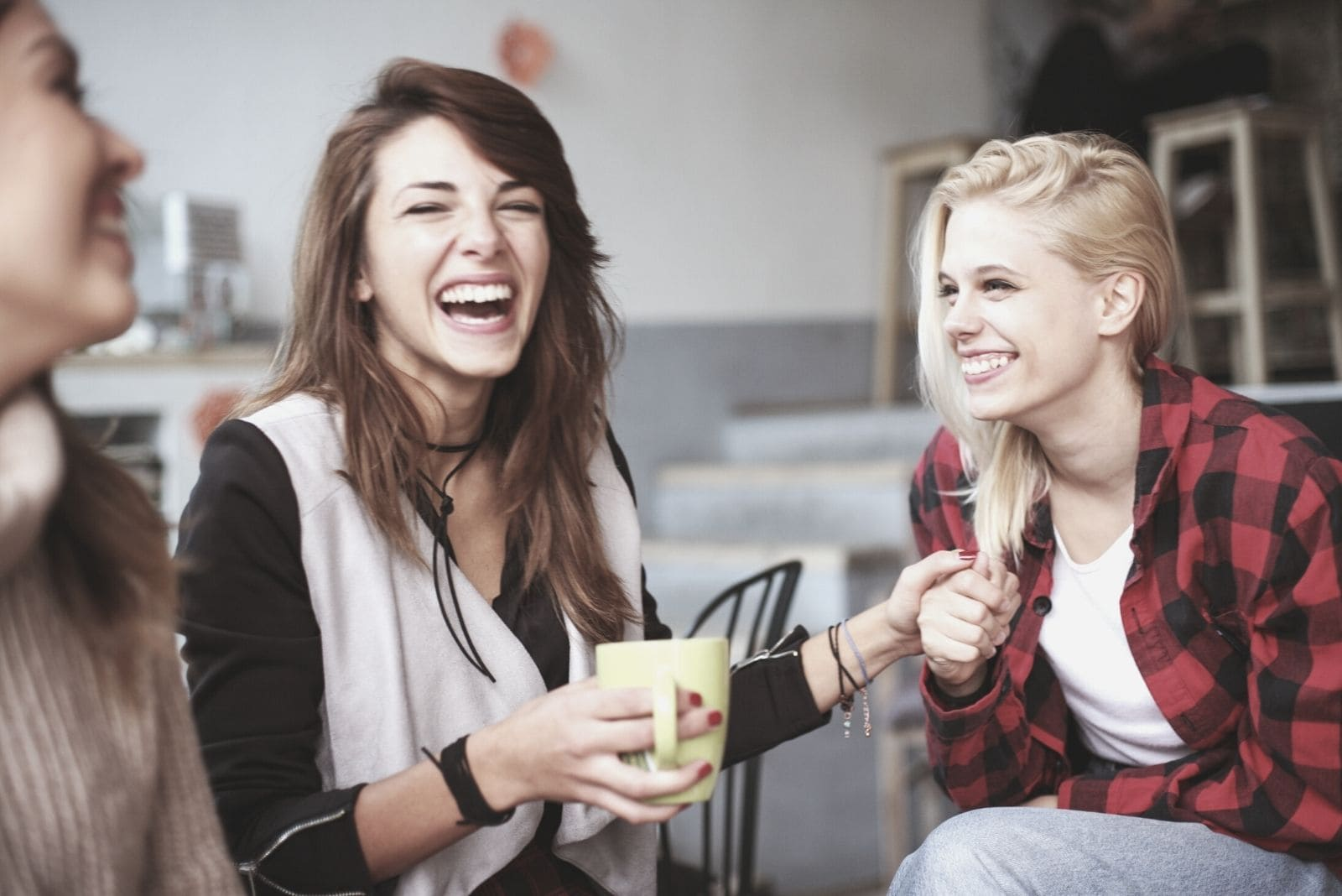 female friends laughing and chatting inside the living room while drinking coffee
