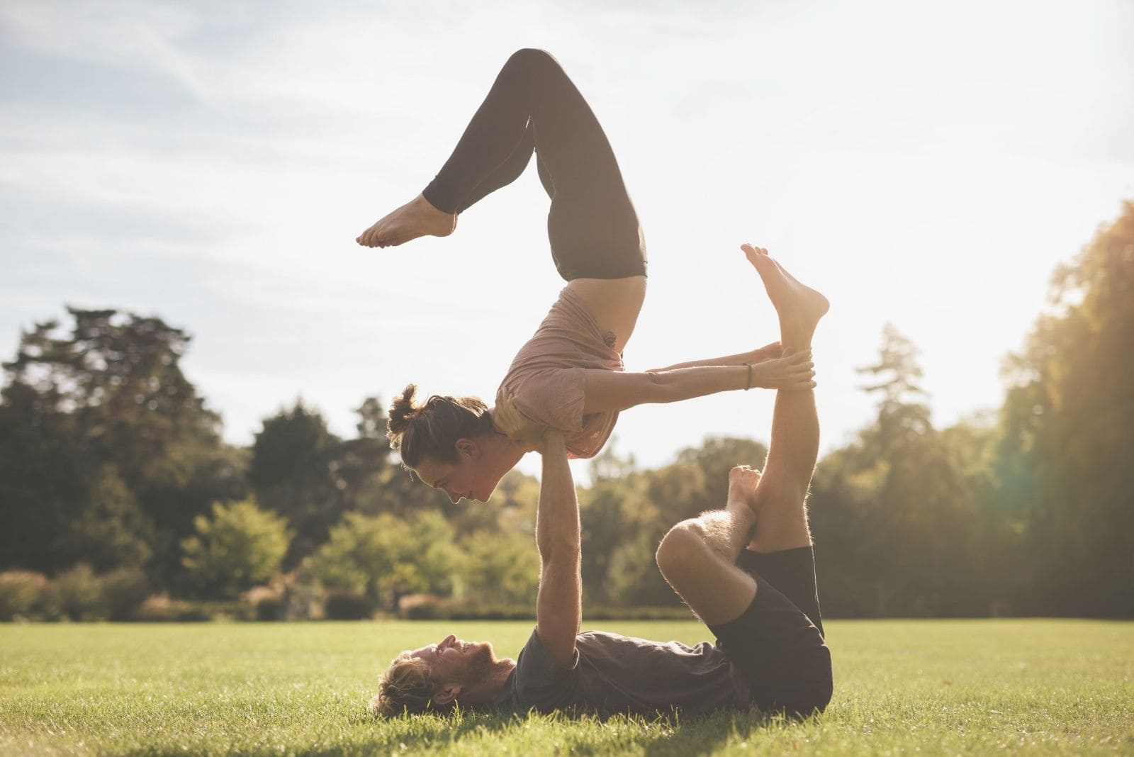 fit young couple doing acroyoga together on grass
