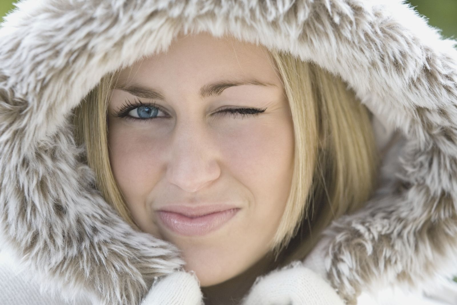 flirting woman looking and winking at the camera wearing a thick fur jacket in close up image