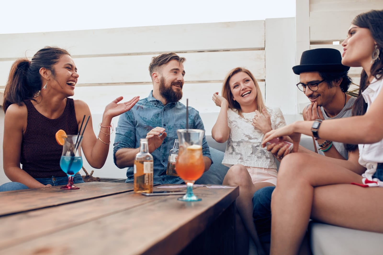 friends talking and drinking while sitting outdoor