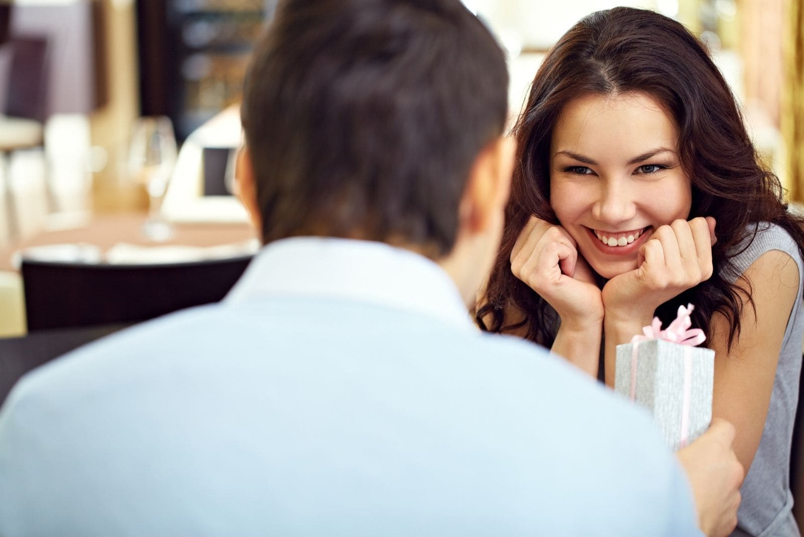 giggling beautiful woman over the gift of the man while having dinner