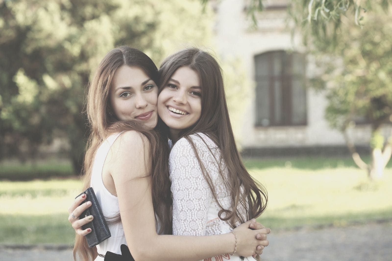 girlfriends hugging outdoors looking at the camera and smiling
