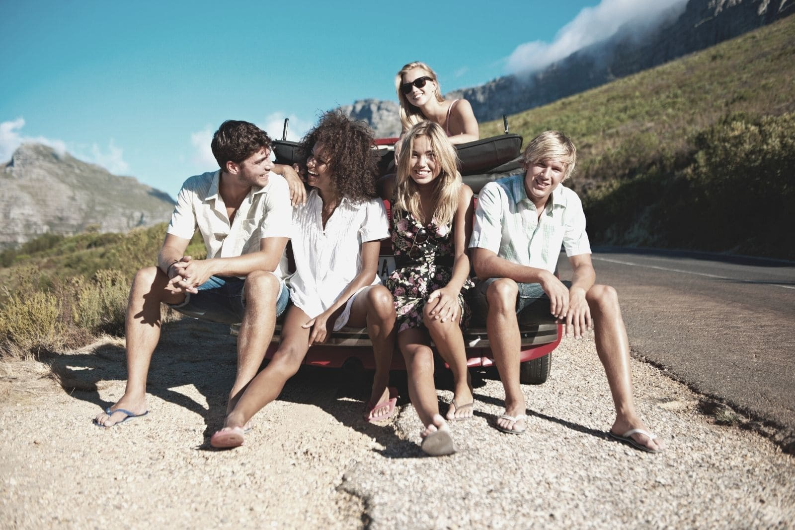 group of young friends sitting on the car bump while on a road trip