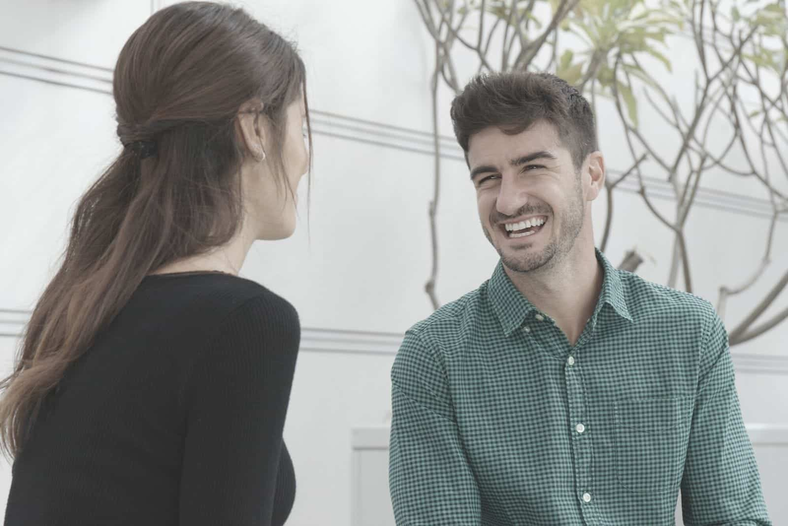 happy and cheerful couple talking outside of their house