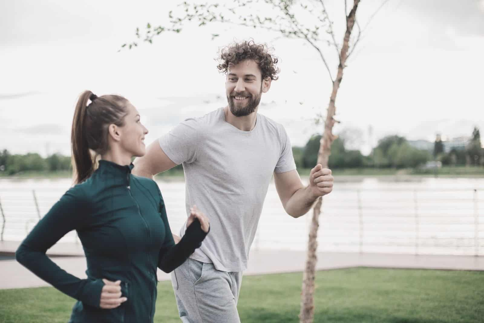 happy athletic couple running and chatting near the body of water
