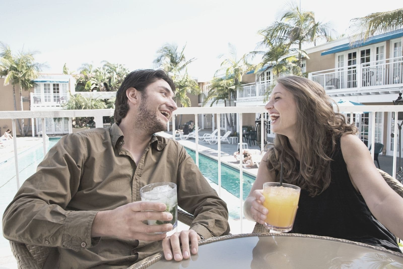 happy couple laughing enjoying each other at the side of the pool drinking beverage by the table