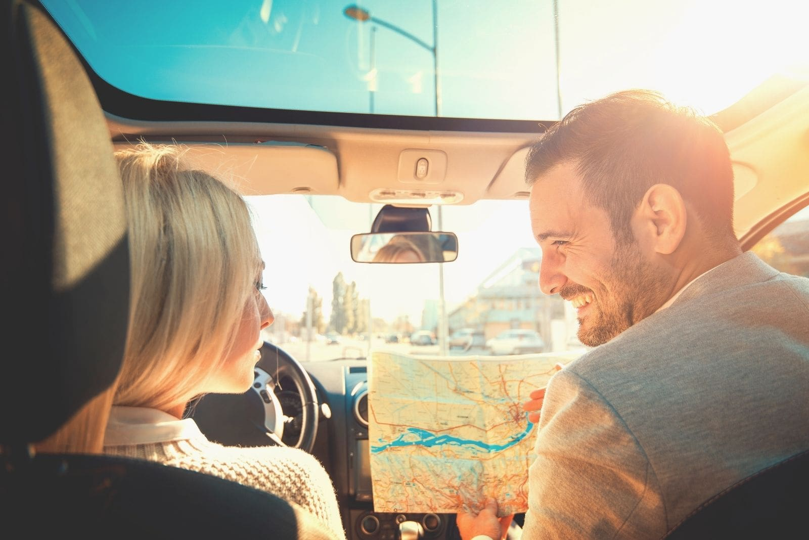 happy couple travelling together inside a car holding a map