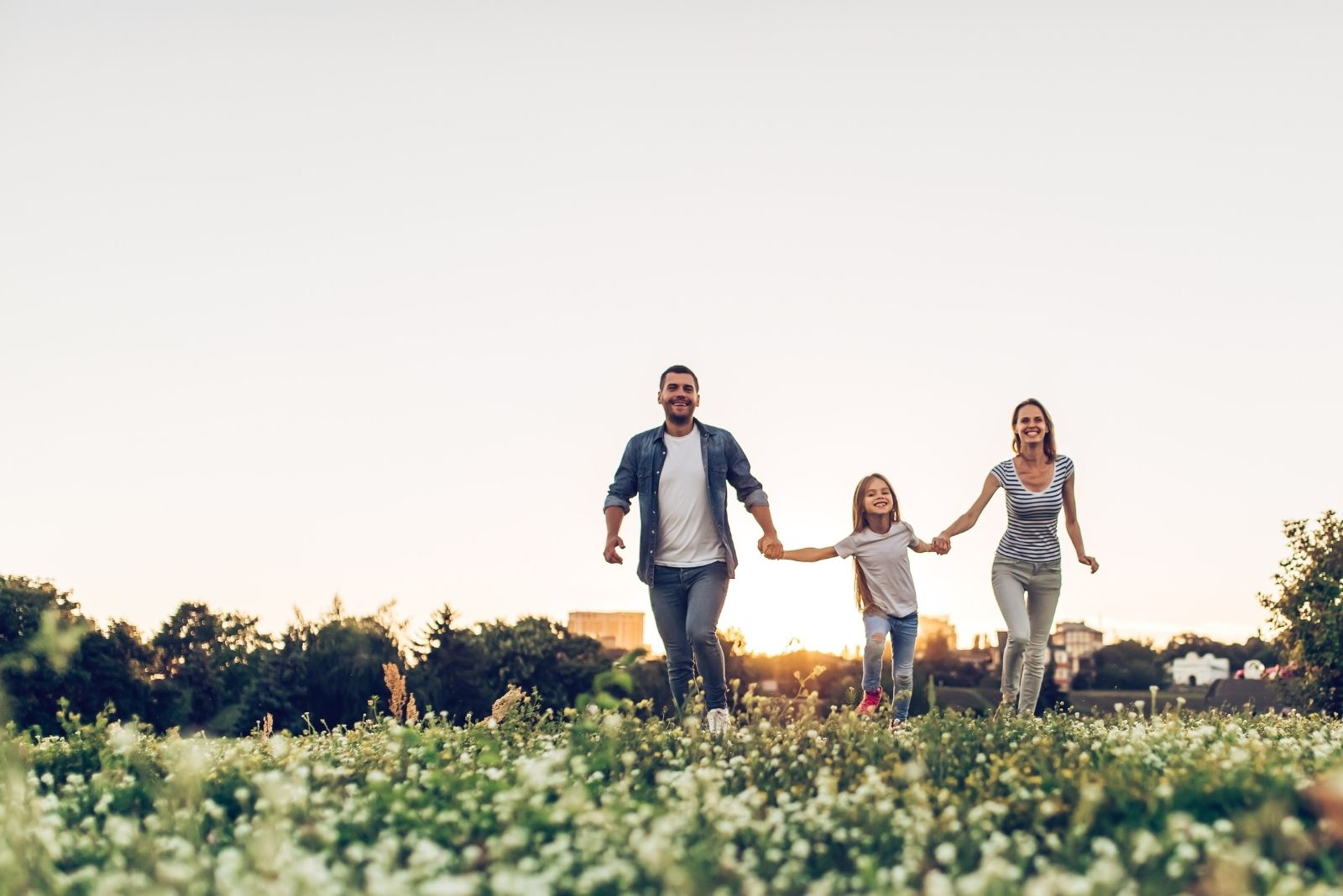 happy family outdoors spending time together in the field holding hands