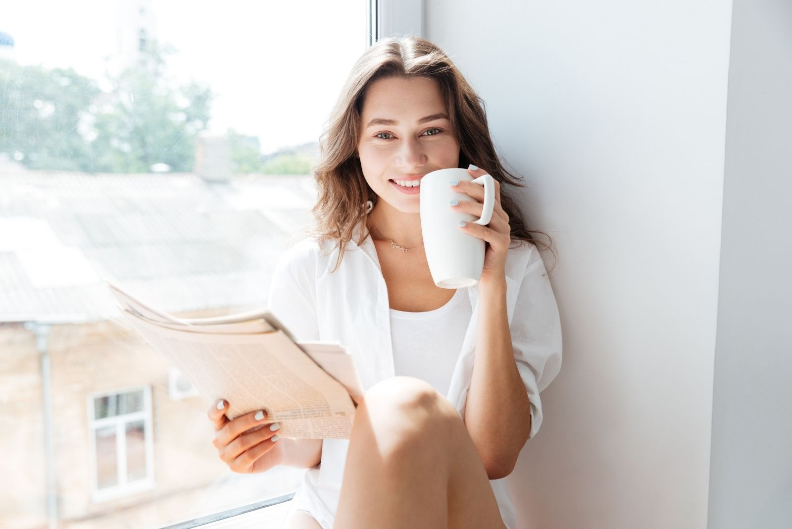 happy woman sitting on the window sill holding newspaper and a mug looking at the camera