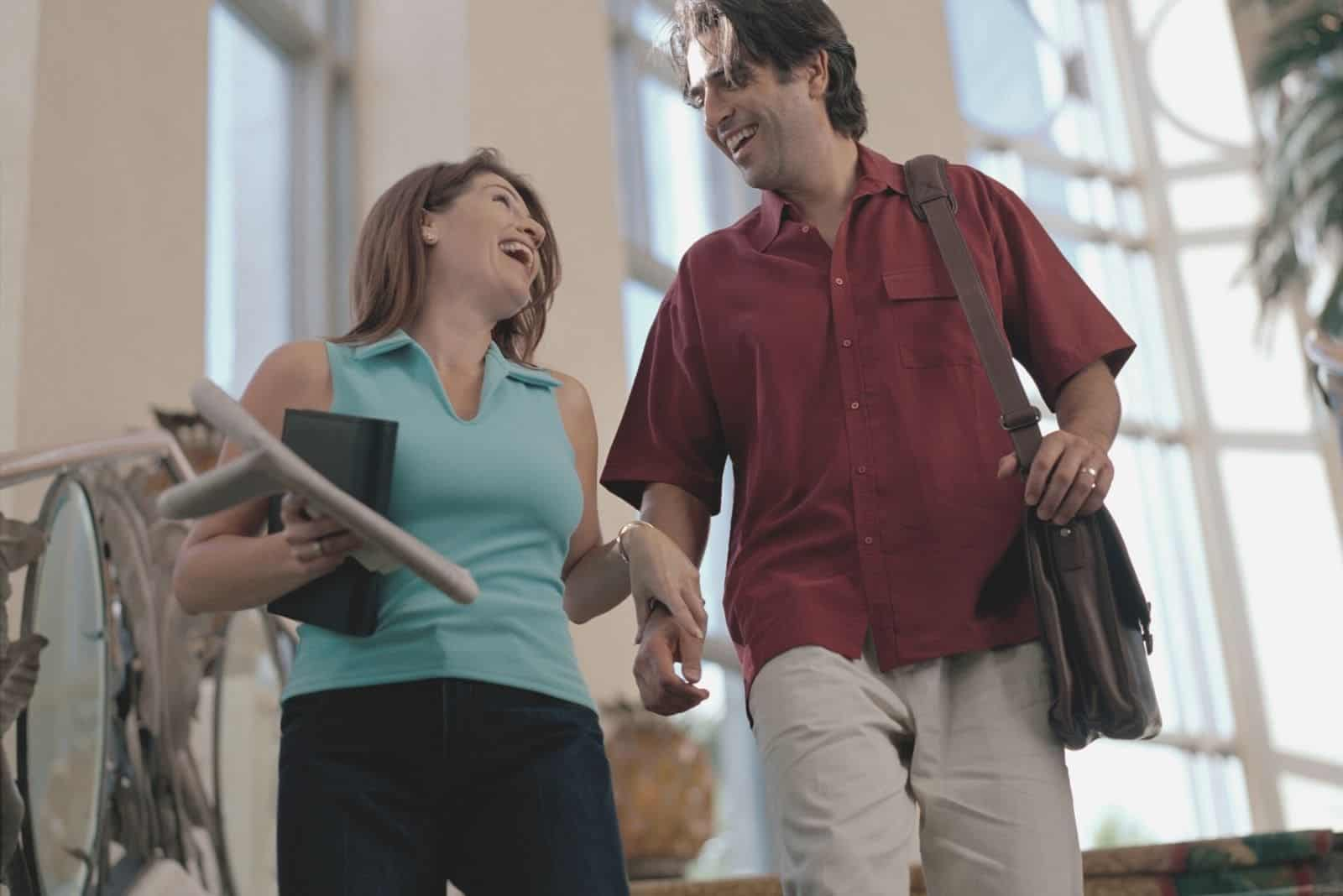 heterosexual couple laughing while walking down the stairs and bringing their stuffs
