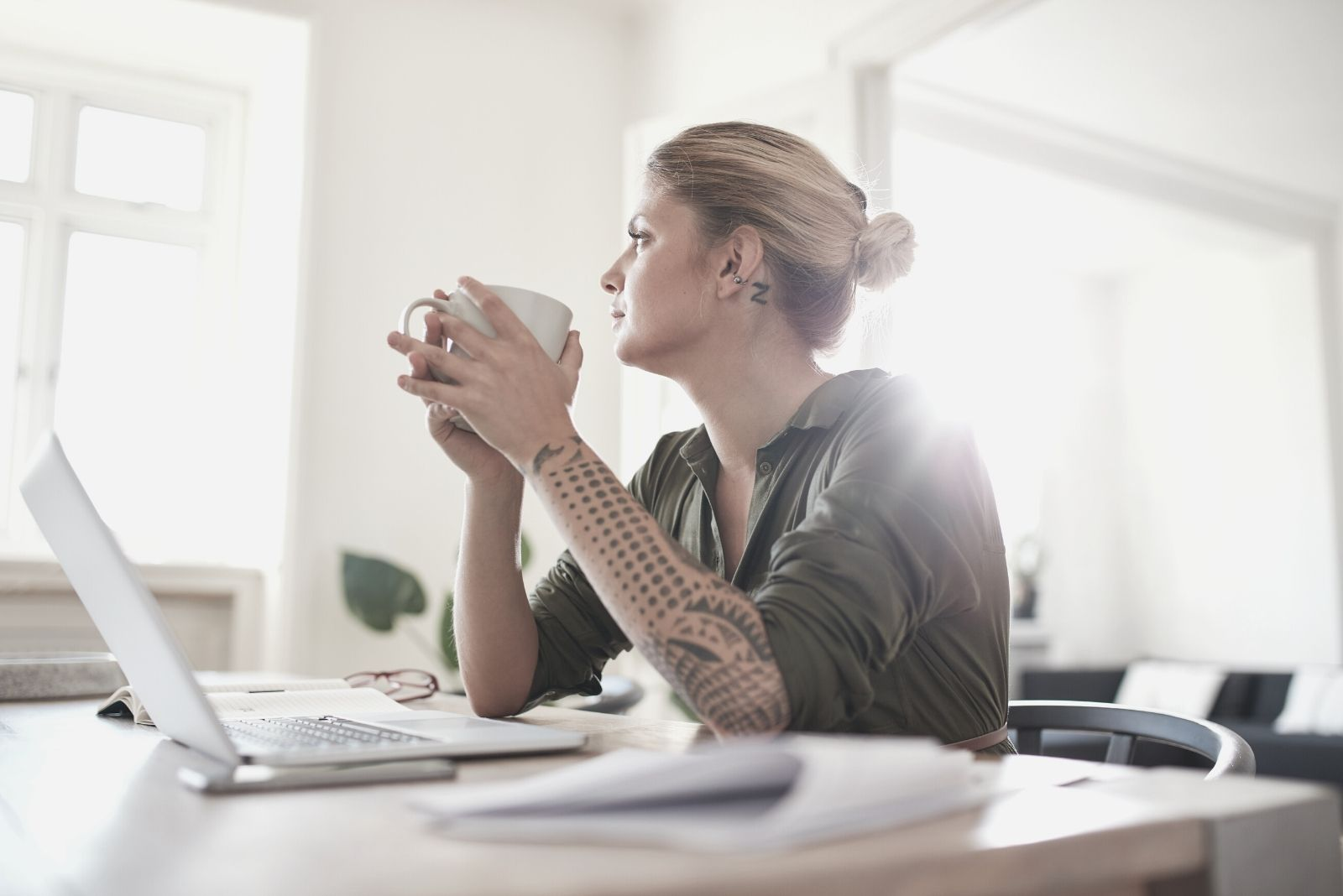 indoor shot of young woman drinking coffee sitting by the table