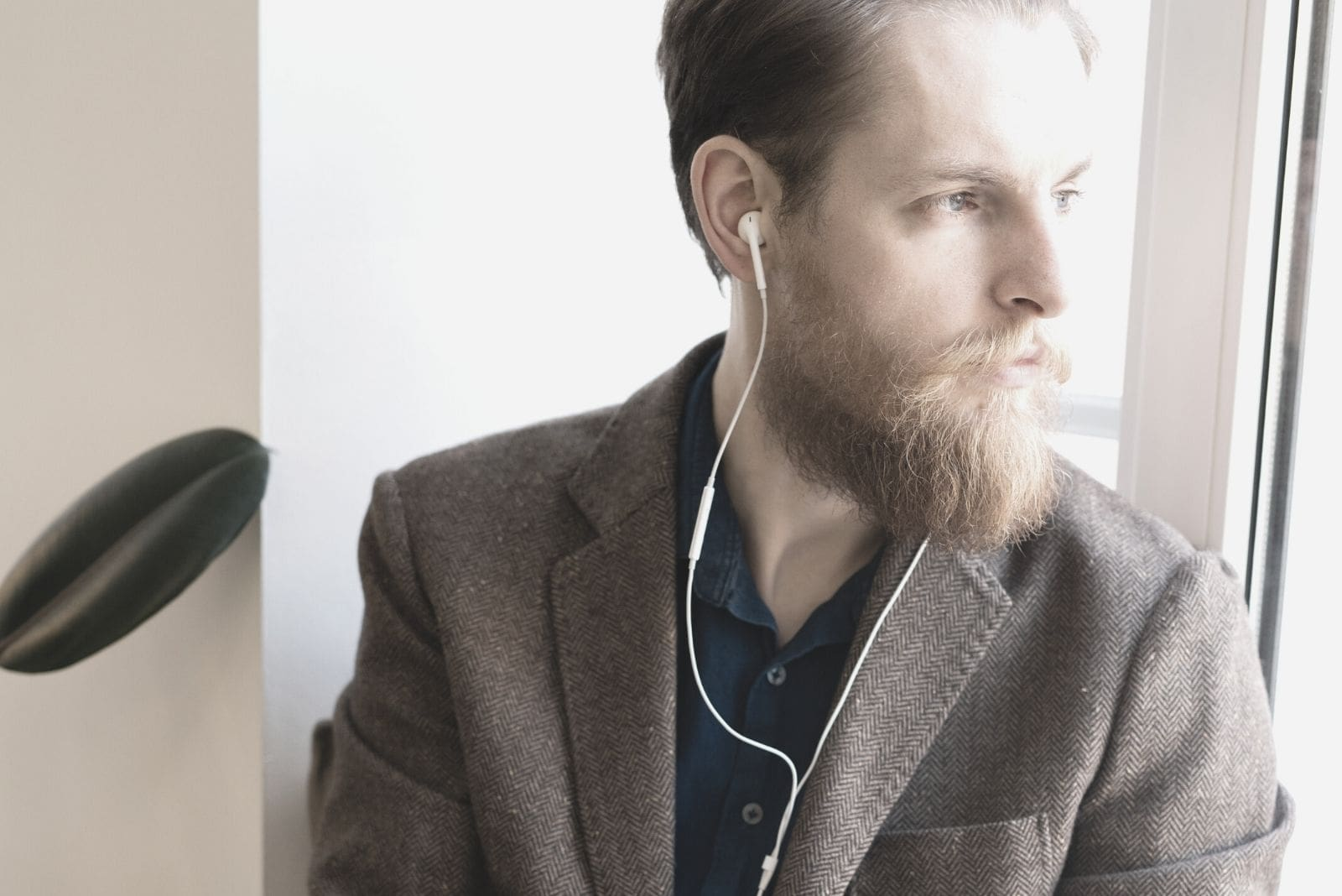 introspective hipster man with beard sitting in the window sill using a earphone