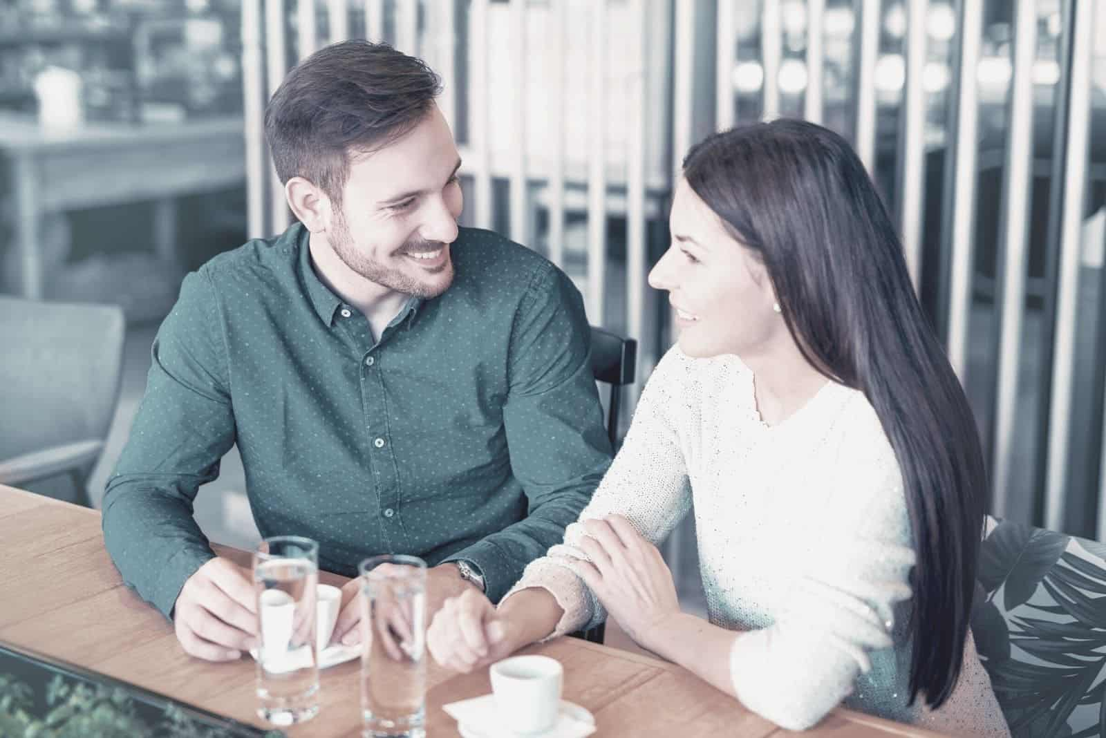 man and woman chatting in an outdoor cafe