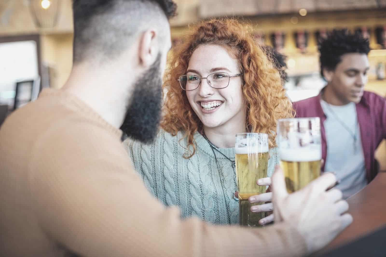 man and woman drinking beer in a bar with friends